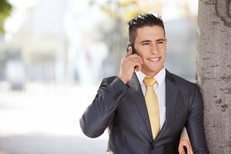 sucessful: Sucessful and handsome businessman talking at his cellphone next to a tree