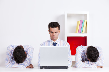 Three twin businessman, one is working with the laptop the other two are sleeping photo