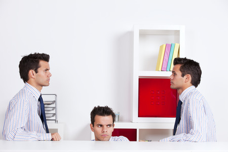 hidden success: Three businessman looking at each other behind the office desk Stock Photo