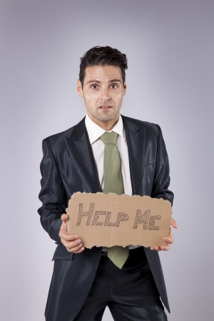 looking for a job: Scared businessman holding a cardboard saying that he need some help