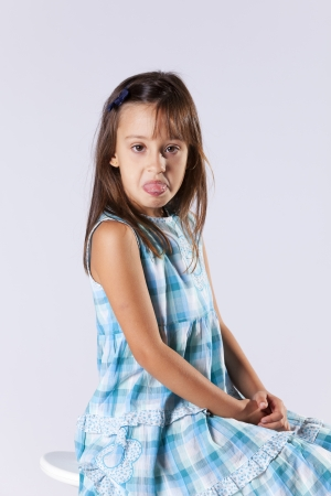 Upset little girl with her tongue out (gray background) photo