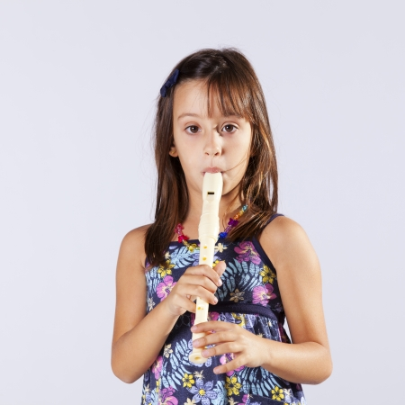 Little girl playing music with a flute photo