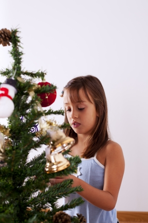 Happy little girl decorating a christmas tree photo