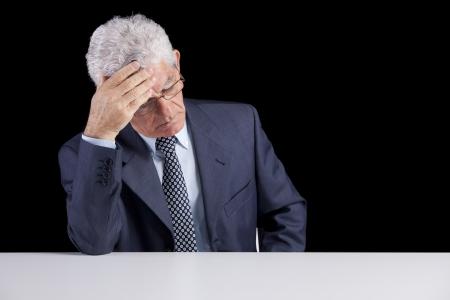 Senior businessman with an headache (isolated on black) photo