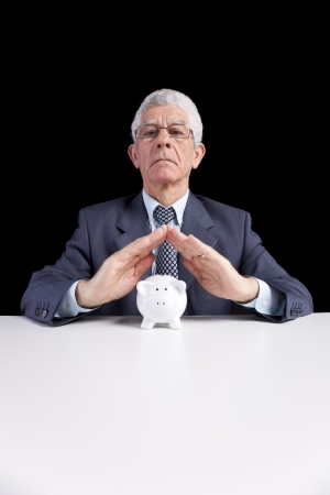 Senior businessman saving some money for his retirement (isolated on black) Stock Photo - 23489305