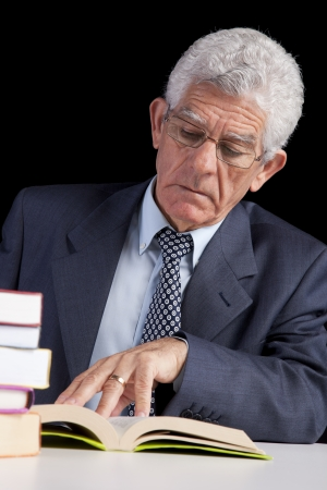 Senior businessman holding a page from an open book (isolated on black) Stock Photo - 23489306
