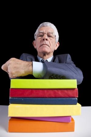 Senior teacher portrait behind some books (isolated on black) Stock Photo