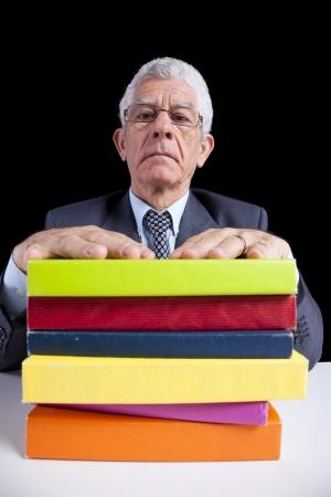 Senior teacher portrait behind some books (isolated on black) Stock Photo - 23489308