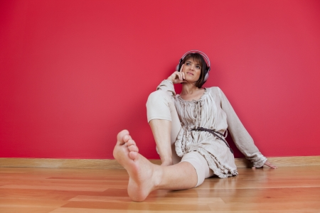 Woman listening to music with headphones sited on the floor at home photo