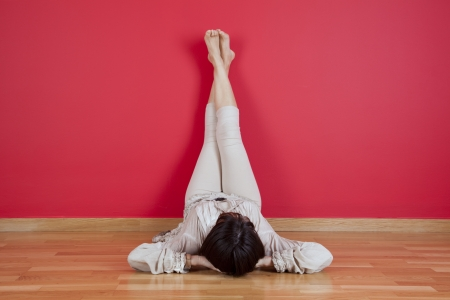 woman laying on the floor of her house next to a red wall Standard-Bild