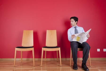 businessman reading the newspaper siting on a chair Stock Photo