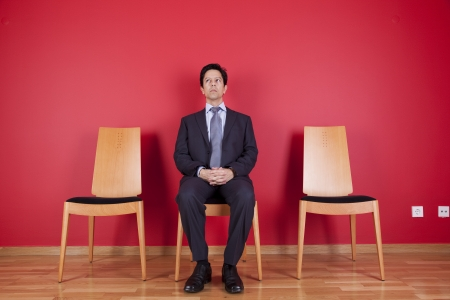 Businessman sited next to a red wall Stock Photo