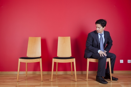 Jealous businessman looking to empty chairs Stock Photo