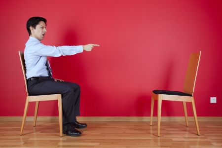 Businessman sited next to a red wall pointing to a empty chair Stock Photo