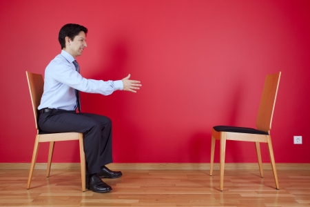 Handshake agreement between a businessman and an chair next to a red wall