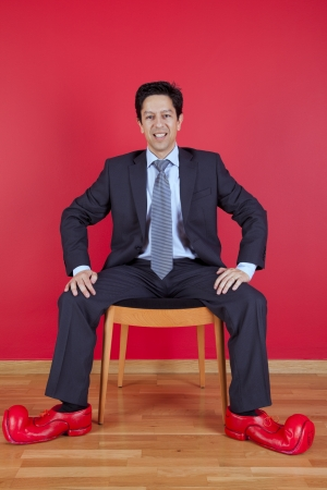 Businessman sited next to a red wall with clown shoes