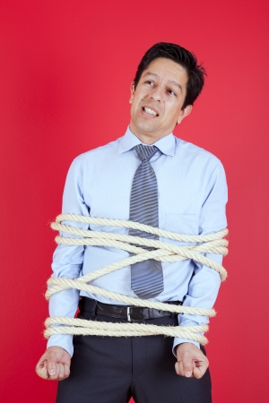 Businessman tied up with a rope struggle to get free