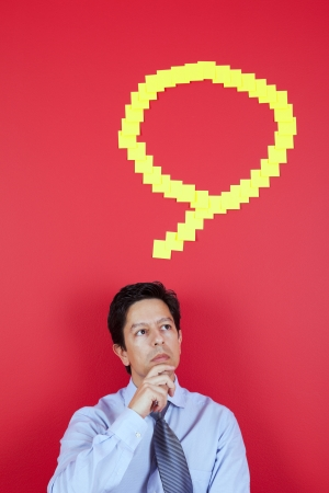 Businessman thinking next to a red wall Stock Photo - 23489350
