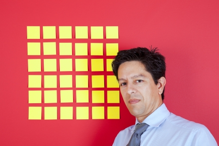 Businessman looking to yellow papers sticked at a red wall photo
