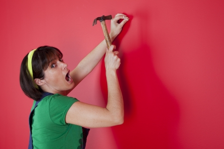 woman driving a nail in a red wall photo