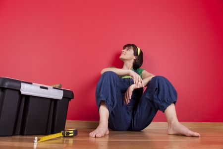 woman relaxing at her house after repairing her red wall photo