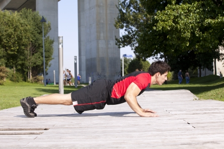 Athlete man at the city park making some pushup