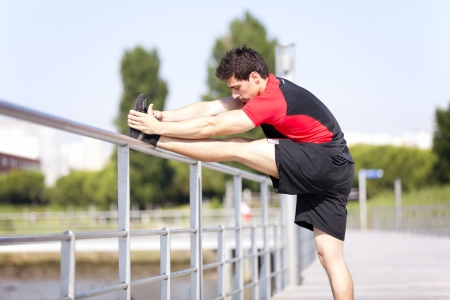 Athlete at the city park warming and stretching Stock Photo