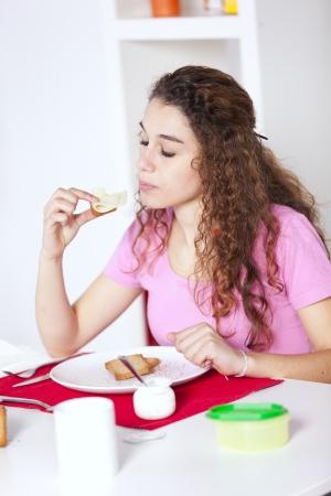 Young beautiful woman eating her morning yogurt Stock Photo