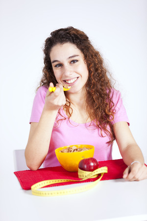 Happy young woman eating cereals