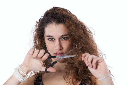 Unhappy woman cutting her hair with a scissor photo