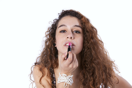 Sensual young woman applying lipstick (isolated on gray) photo