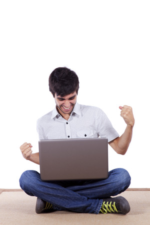 siting: young man surfing the internet in his laptop sited on the carpet (isolated on white) Stock Photo
