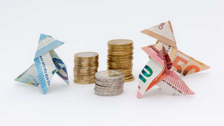 Three origami birds made of 10, 20 and 50 euro banknotes, around stacks of euro coins, white background Banque d'images