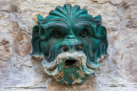 Ancient bronze sculpture representing the head of a gargoyle, on the background of a stone wall. Fountain of St. Jean square, Lyon, France