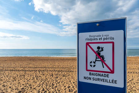 Sign written in French indicating an unpatrolled beach. Atlantic coast, Anglet, France Stock fotó