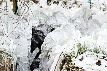 frozen creek: ice area and icicles in a frozen creek Stock Photo