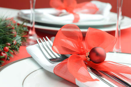 christmas dish: Decorated christmas table setting in festive red white colours, napkin cutlery tied with organza ribbon and holiday bauble
