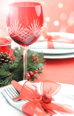 Christmas table setting and festive seasonal lighting bokeh in traditional red and white with plates, cutlery, wine glasses photo