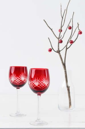 Red festive christmas wine glasses on table with minimalist christmas tree photo
