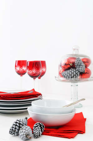 Casual christmas table setting crockery display in red and white theme, pine cones, xmas baubles decorations Stock Photo - 15531366