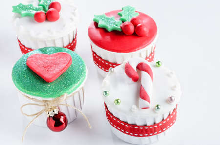 Holiday festive christmas theme mini cup cakes with shiny decorative balls and ribbons  Stock Photo - 15531371