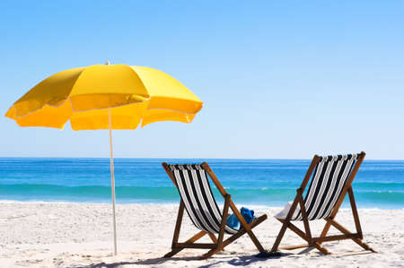 Pair of sun loungers and a beach umbrella on a deserted beach; perfect vacation concept  photo