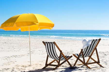 비치 의자와 밝은 햇빛과 모래에 노란 우산 스톡 사진