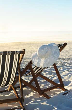 silla playa: Gorro para el sol colgando de la silla de playa en la arena en la puesta del sol, un concepto de vacaciones o de jubilaci�n Foto de archivo