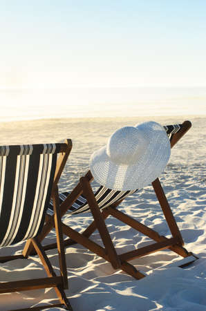 strandstoel: Zonnehoed opknoping van strand stoel op zand bij zonsondergang, een vakantie of pensioen begrip Stockfoto