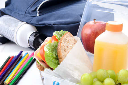 Lunchbox with ham sandwich and fruit with schoolbag and coloured pencils  photo