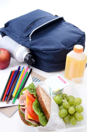 Healthy lunchbox with wholemeal ham sandwich, fruit, yogurt and orange juice  photo