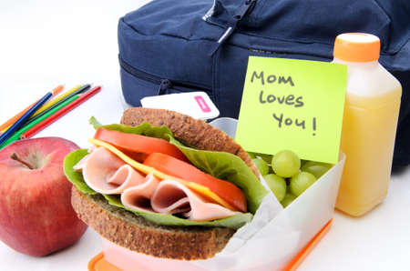 Fresh sandwich and apple with schoolbag and post-it note  photo