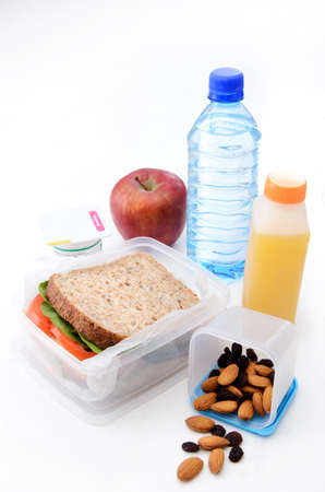 Healthy packed lunch with wholemeal sandwich, apple, dried fruit, nuts and yoghurt isolated on white  photo