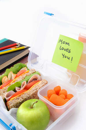 Surprise postie message in school lunch box filled with sandwiches and healthy food photo